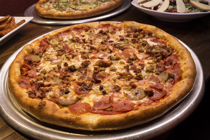 Meat lovers pizza with assorted appetizers surrounding
