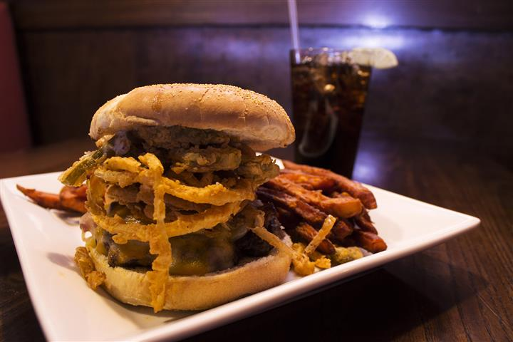 Cheese burger with fried onions and pickles with French fries and a glass of soda in the background