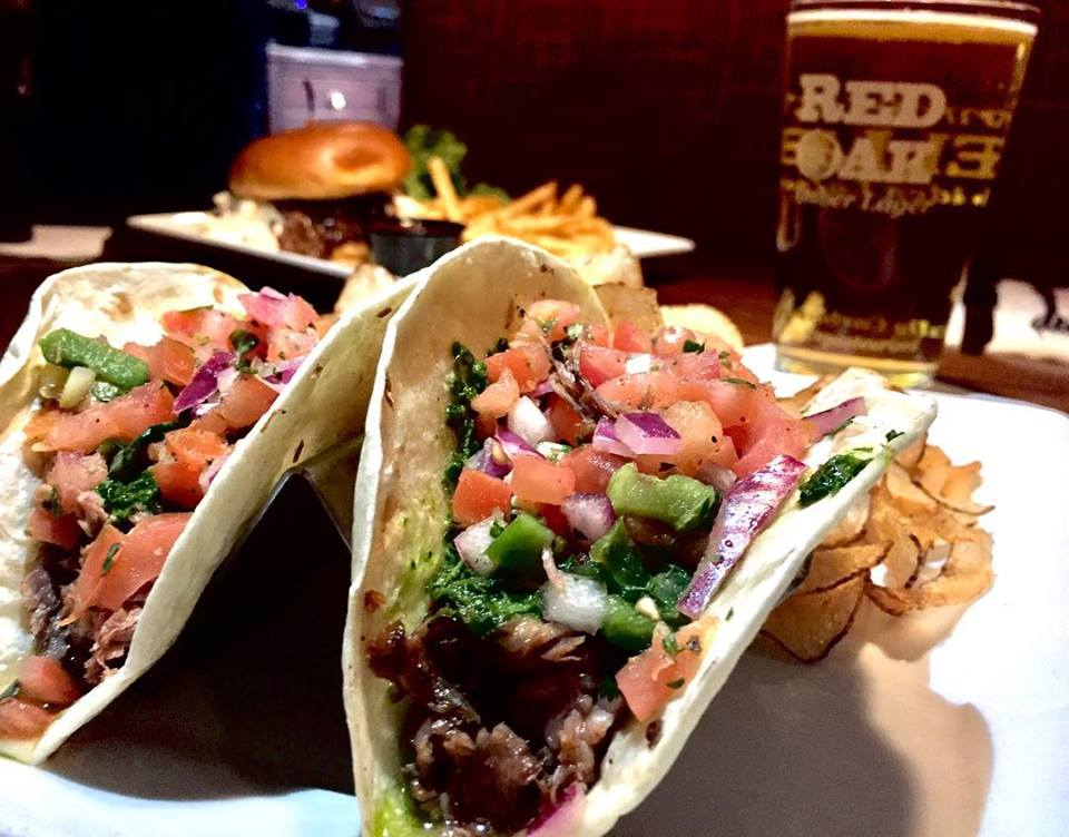 Two steak tacos with pico de gallo on a plate with chips and a pint of beer and cheeseburger in the background