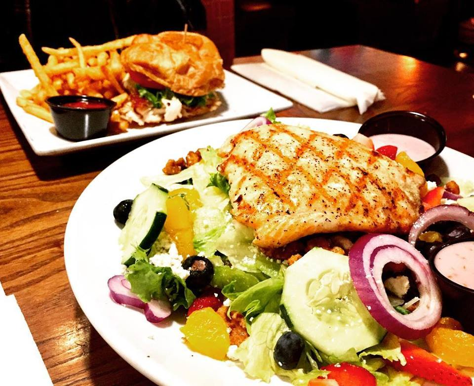 Grilled chicken salad with a cheese burger and fries on a plate in the background