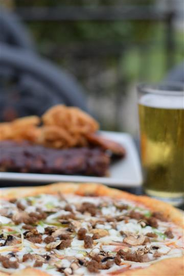 Sausage pizza with mushrooms and green peppers, a pint of beer and baby back ribs blurred in the background