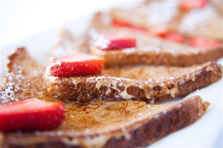 french toast topped with syrup and strawberries