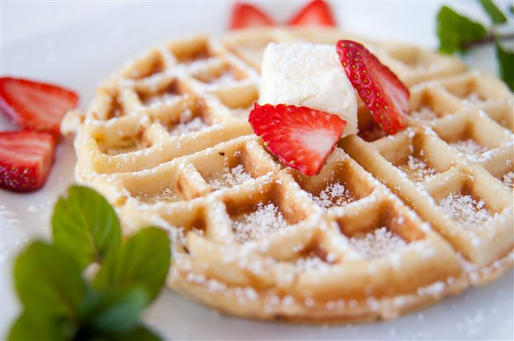 waffle topped with butter and a few strawberries