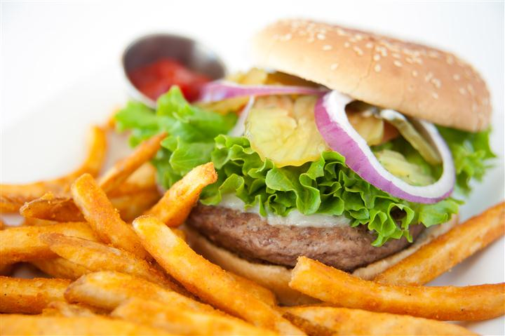 hamburger with lettuce onion and a side of fries