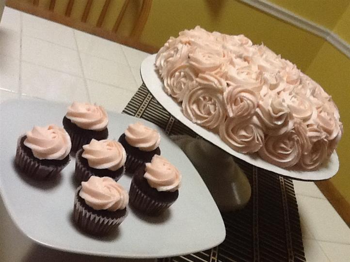 cake decorated with roses and cupcakes topped with icing