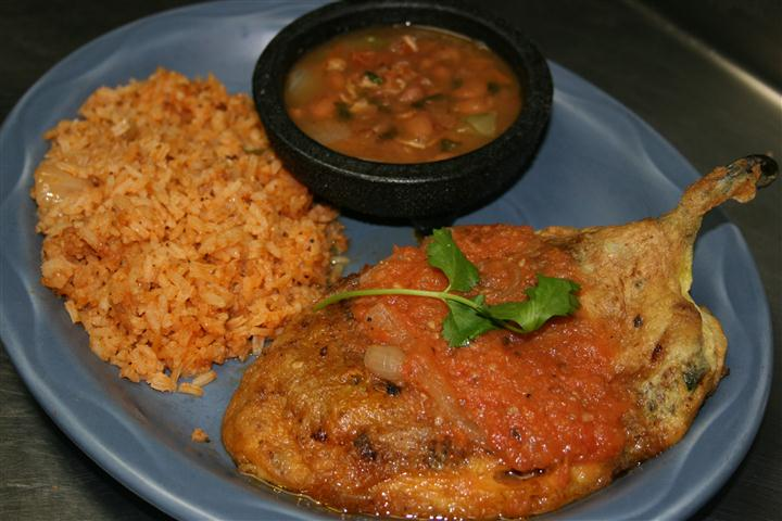 chicken breast covered in red sauce with brown rice and beans on the side
