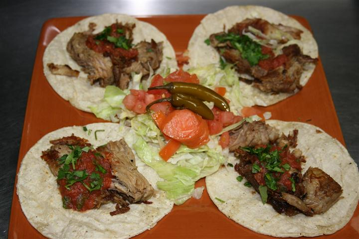 a plate of soft shell tacos with beef, lettuce, tomatoes and peppers