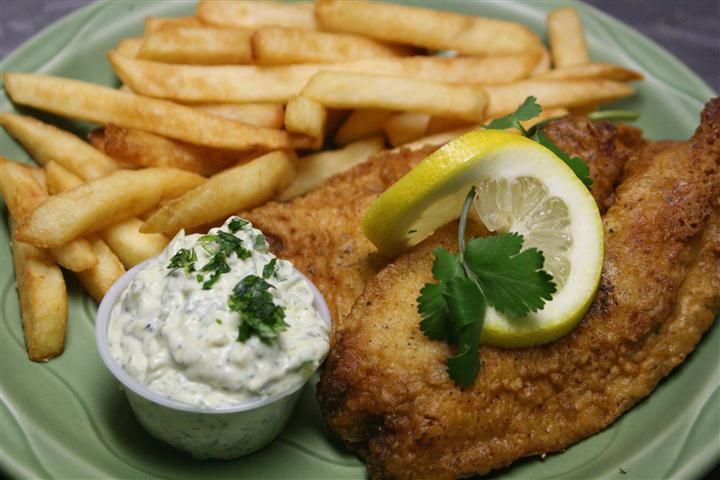 fish with tartar sauce and a side of french fries