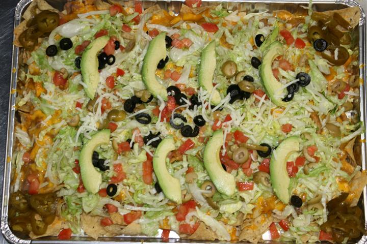tray of tortilla chips covered in dip and topped with lettuce