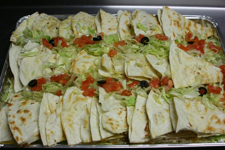 tray of quesadillas covered with lettuce