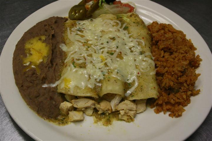 chicken burritos covered in melted cheese with brown rice and beans