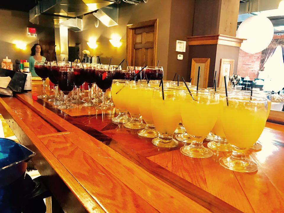 mimosas and sangria lined up on the bar ready to be served for a large party