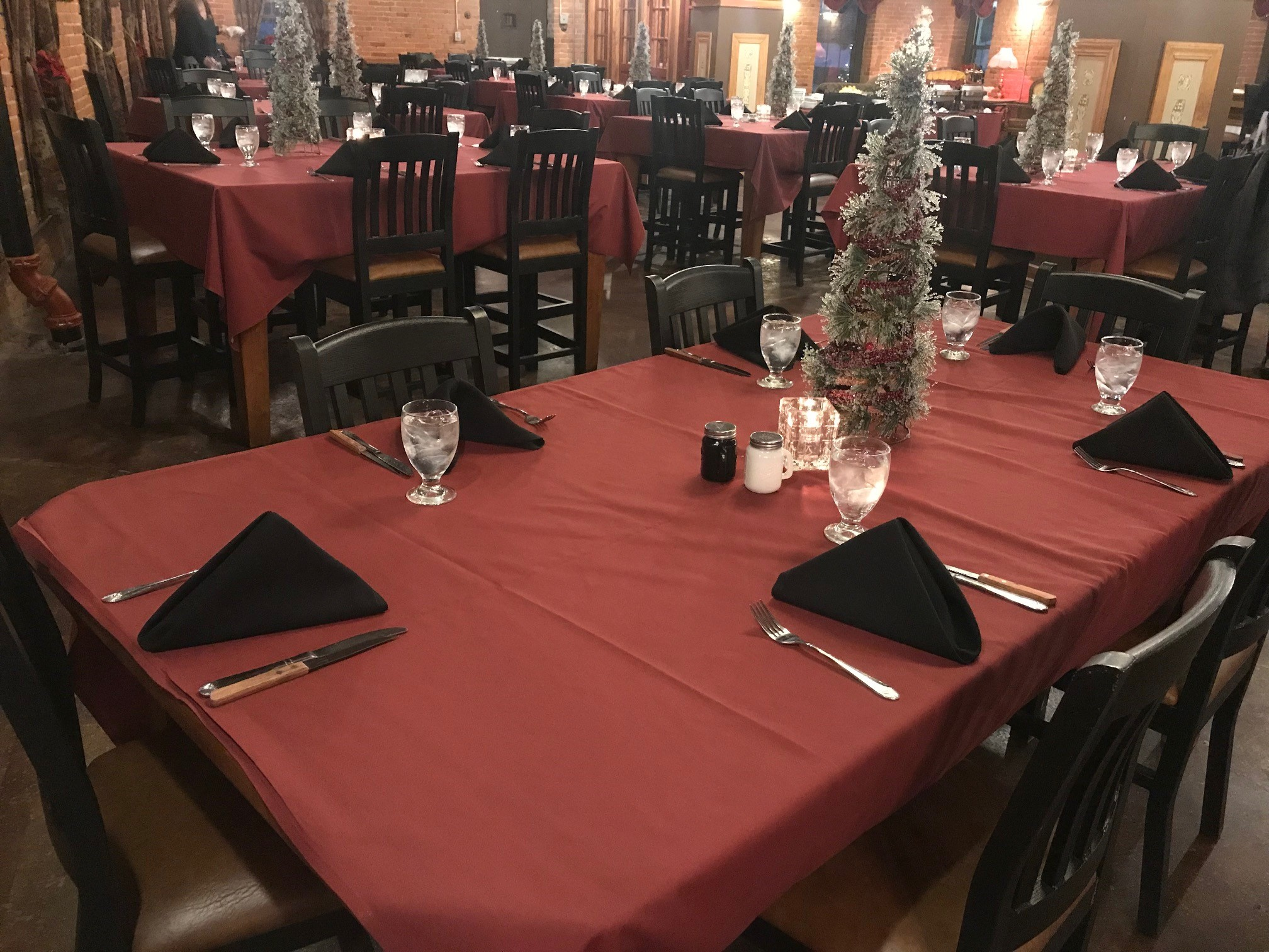 inside view of the restaurant with multiple tables and mini christmas trees on the table as centerpieces