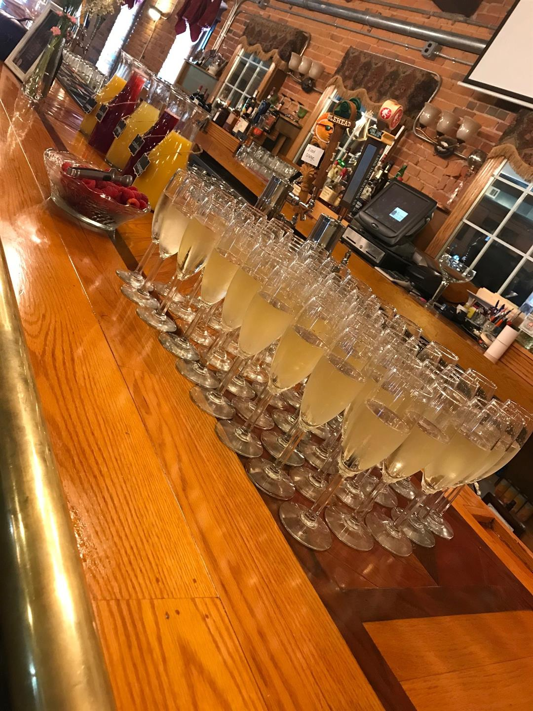 multiple filled champagne glasses on the bar