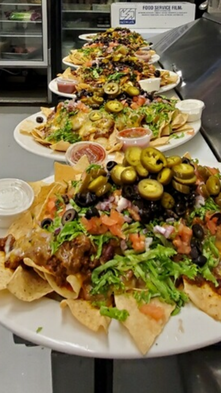 nachos with lettuce, tomato, onions, black olives, jalapenos, side of salsa, side of sour cream