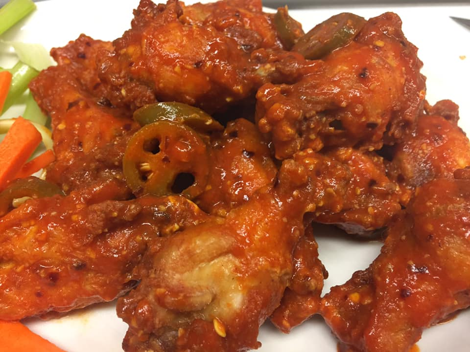 a plate of wings with jalapenos on top
