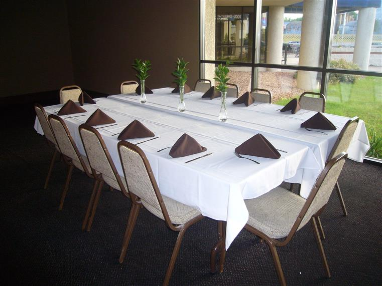A setup table with white cloth, silverware, and glassware