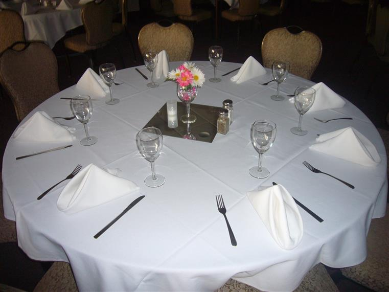 Event table set up with white cloth and silverwear and glasses