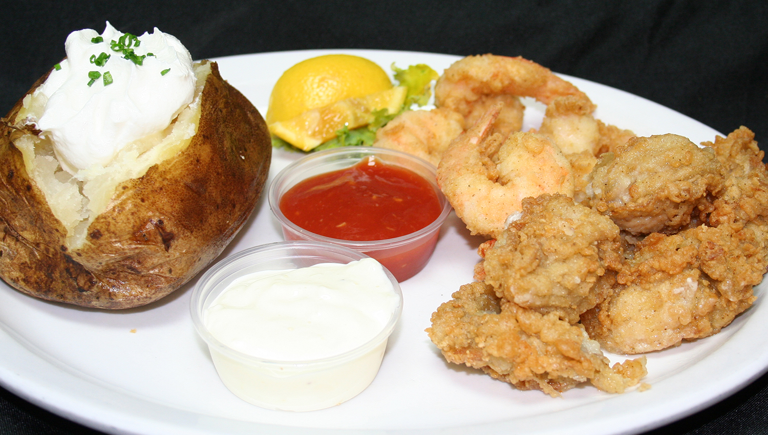 fried combo platter with a baked potato and dipping sauces