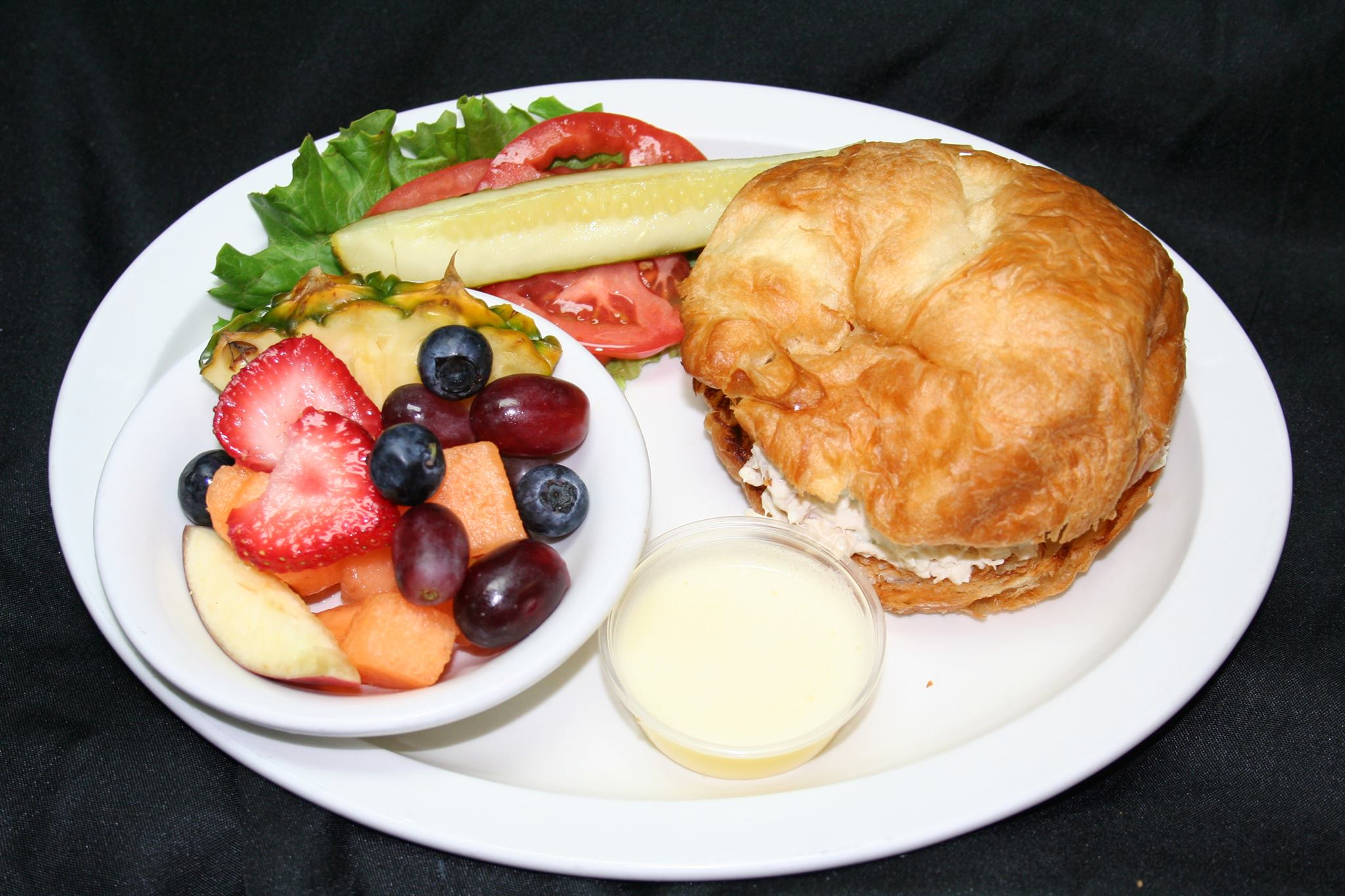 chicken salad on a croissant with fruit on the side