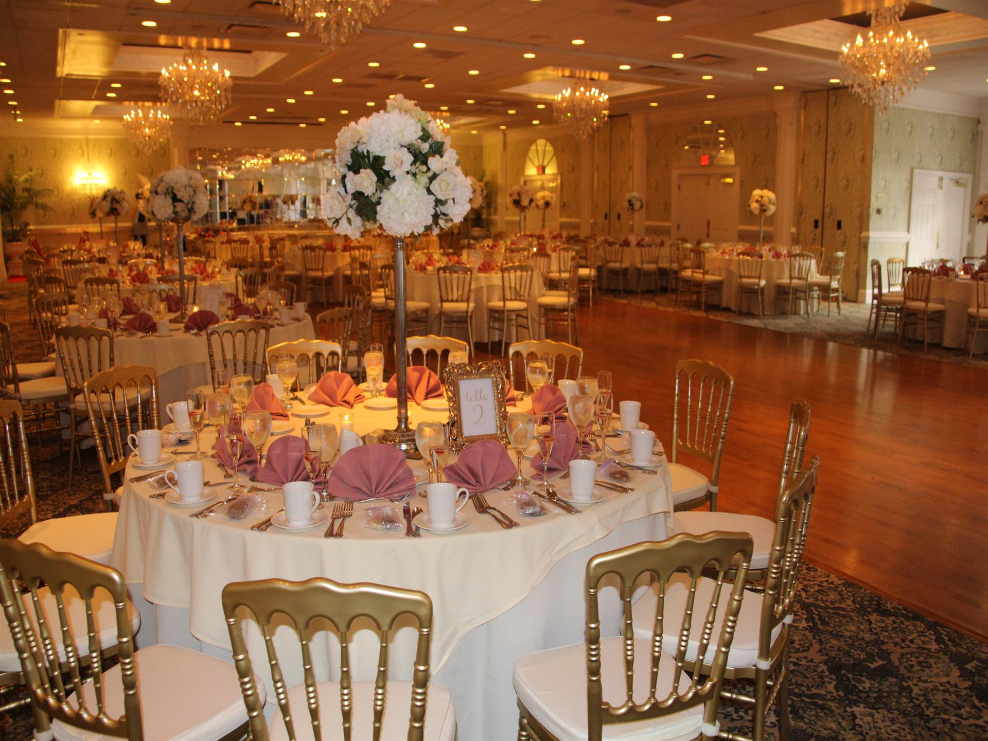 multiple decorated tables and chairs in the banquet room