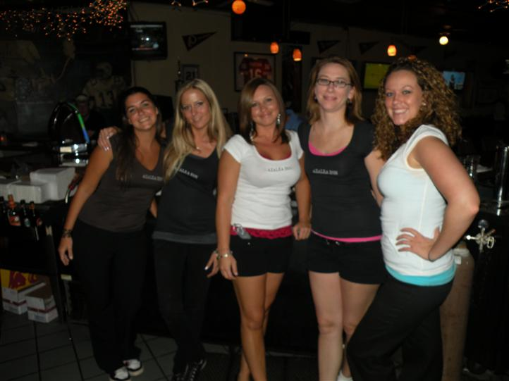 Five young women smiling posing for photo in front of the bar