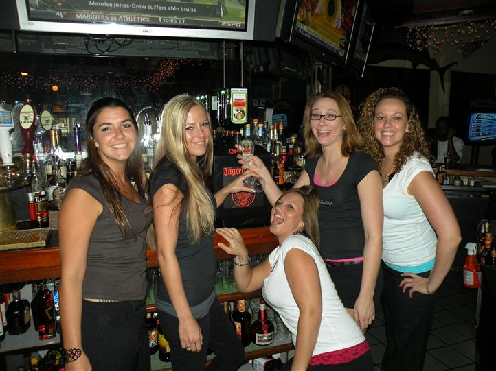 Five young women smiling posing for photo in front of the draft beers