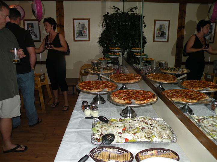 A buffet dinner with pizzas and salad