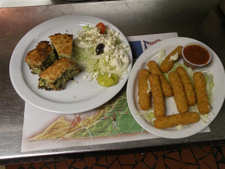 Spanakopita served with side salad and a pickle, and mozzarella sticks served with red sauce