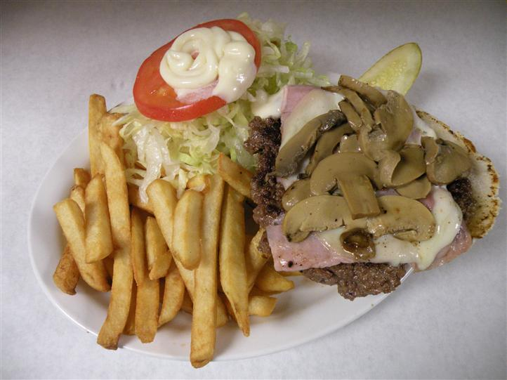 Open faced burger topped with bacon, cheese and mushrooms, served with side salad, French fries and a pickle