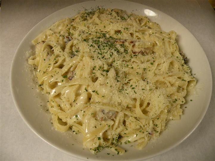Tagliatelle with bacon and white sauce, topped with shredded cheese