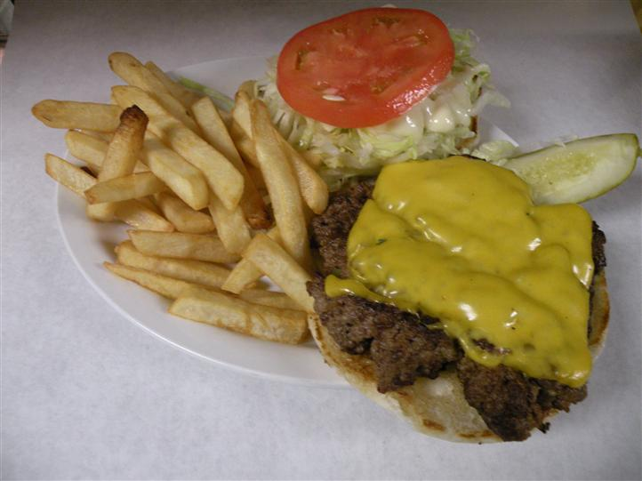 Open faced cheeseburger served with side salad and French fries