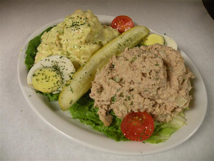 Tuna salad and Potato salad served with a hard boiled egg, cherry tomatoes and a pickle