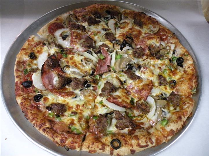 Pizza topped with meat, bacon, olives, onions, sauce, and cheese