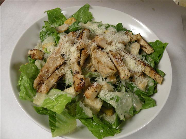 Fresh Romaine lettuce salad topped with grilled chicken and shredded cheese