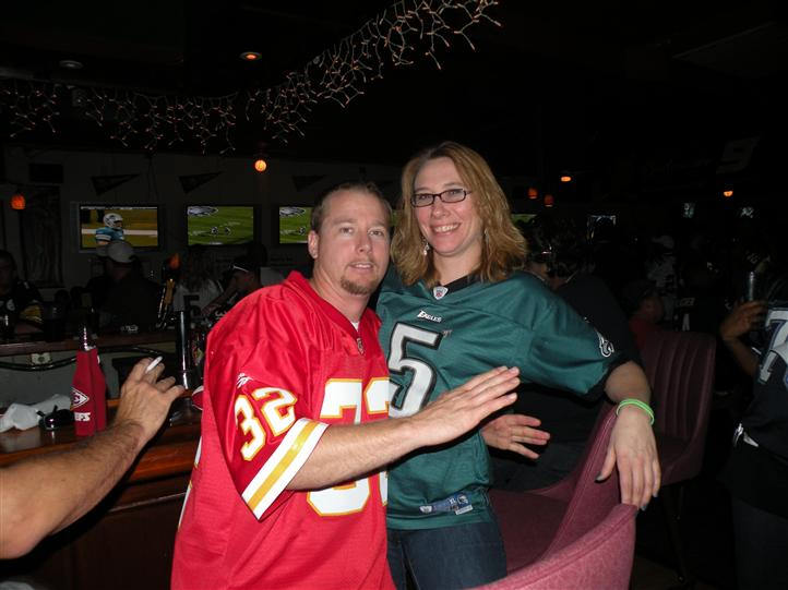 A smiling couple in front of the bar posing for photo, while they are watching a football game on the tv