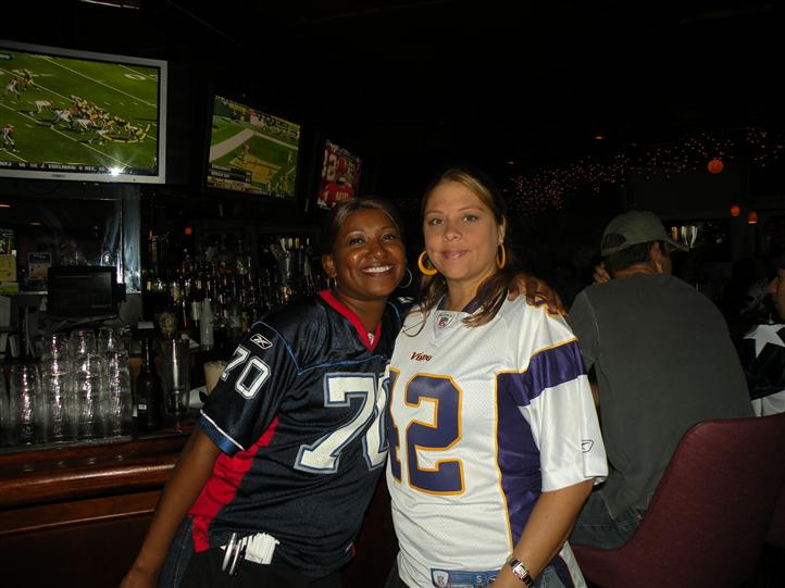 Two smiling women in front of the bar posing for photo, while they are watching a football game on the tv
