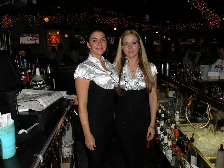 Two smiling waitresses behind the bar posing for photo