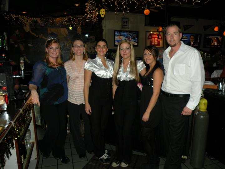 Five women and a man smiling posing for photo in the bar