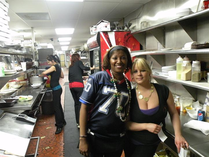 Two smiling young women in the kitchen posing for photo