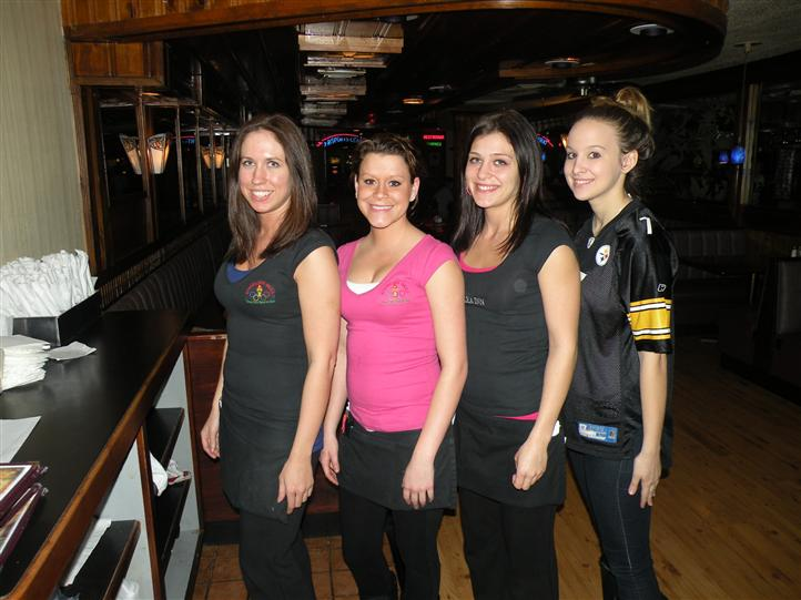 Four smiling young women in the restaurant posing for photo