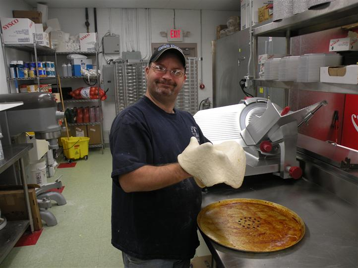 A Smiling man pizza making pizza dough