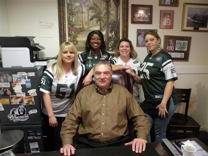 A middle aged man with  four women smiling posing for photo