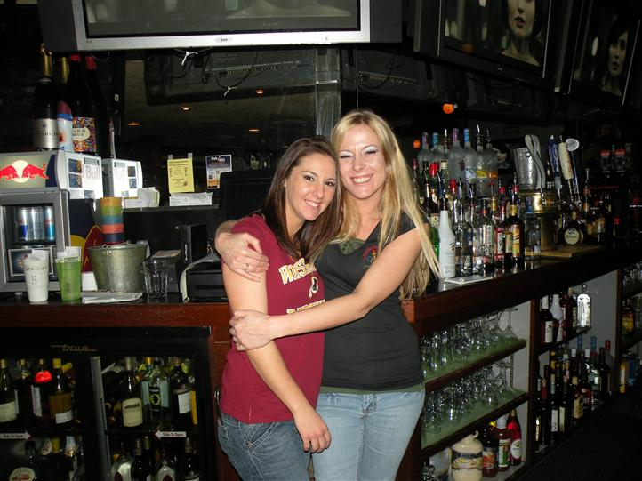 Two smiling young women in front of the bar posing for photo