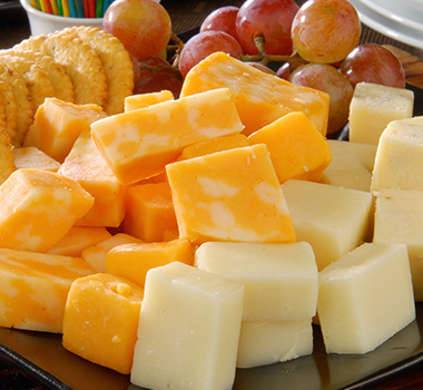 assortment of various cheese, crackers and grapes