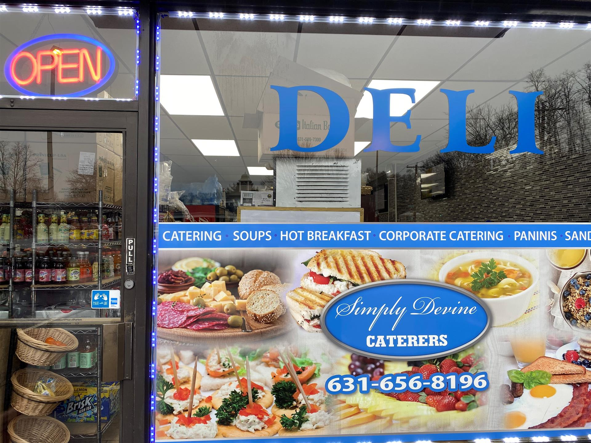 "deli storefront, with pictures of food and a neon ""Open"" sign"