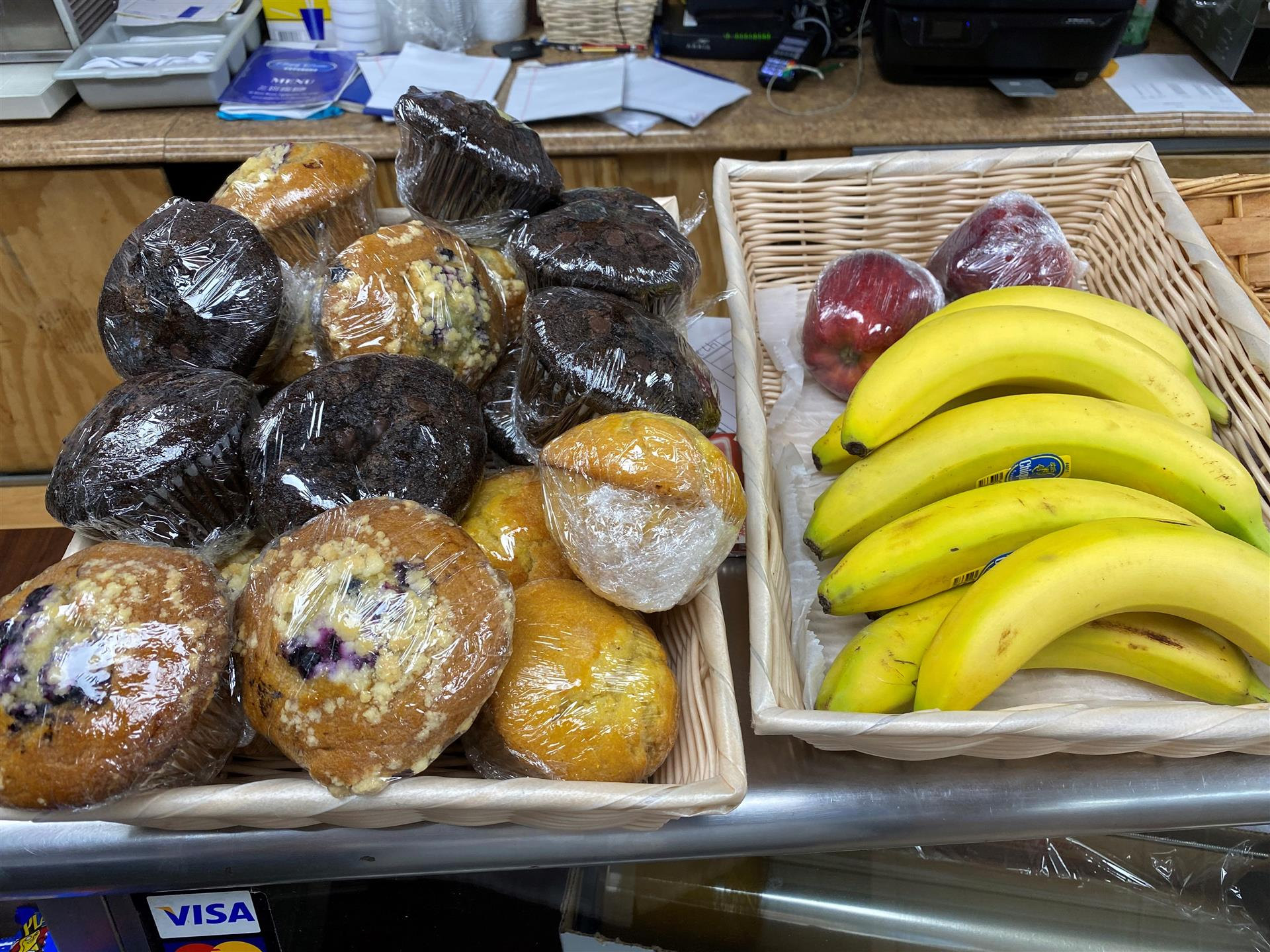 individually wrapped muffins and fruit in baskets