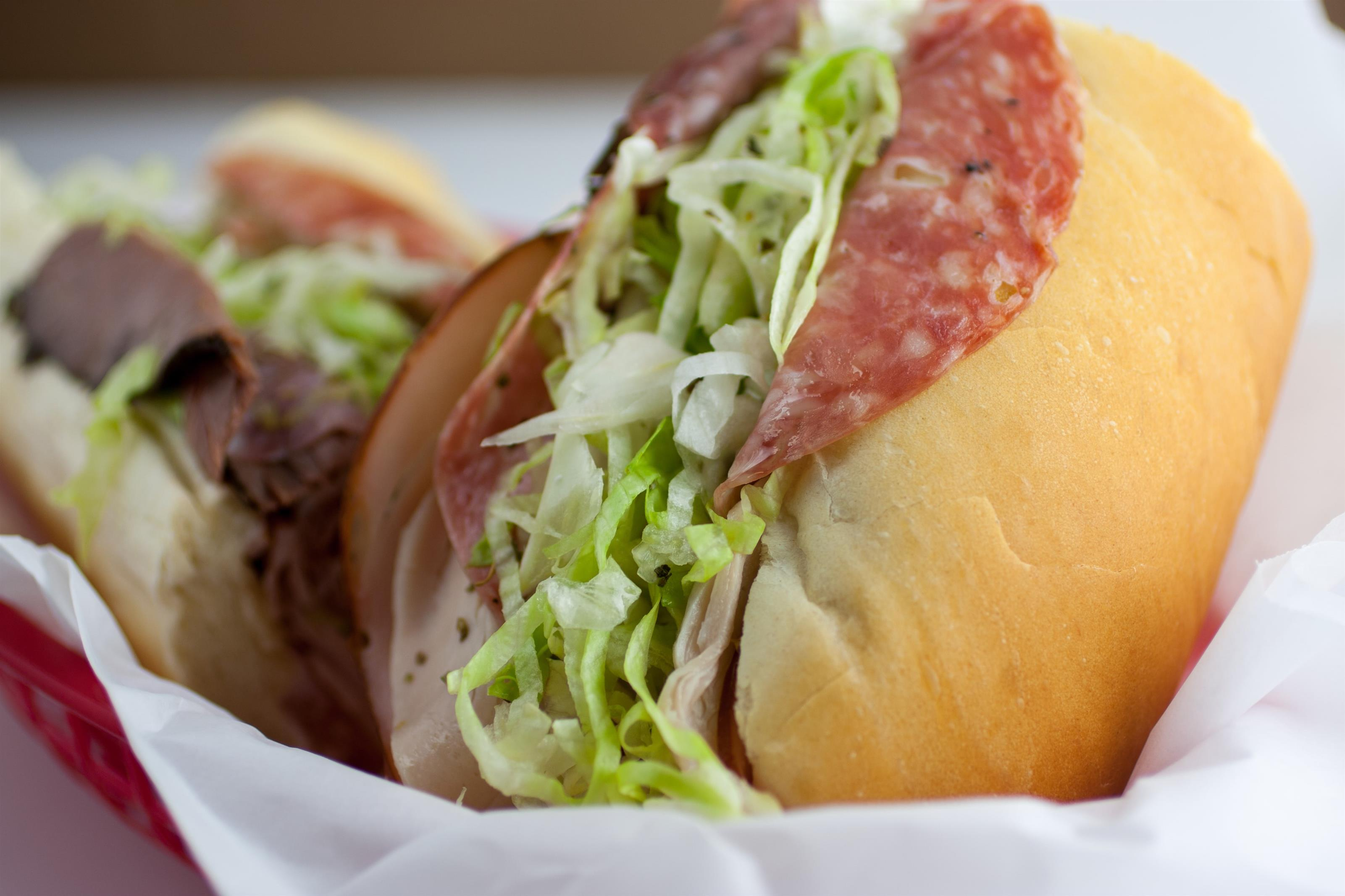 An Italian sub with salami, turkey and lettuce