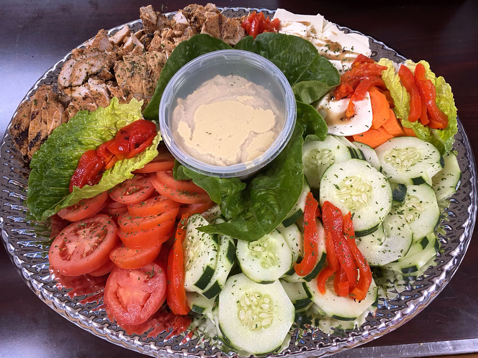 A chicken and vegetable Greek platter with hummus in the center