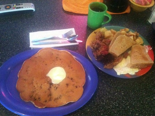 Pancake with butter on plate and eggs with toast and bacon on plate